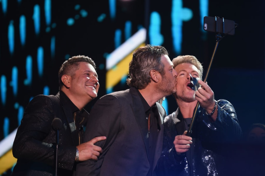 NASHVILLE, TN - JUNE 06:  Jay DeMarcus (L) and Joe Don Rooney (R) of Rascal Flatts pose for a selfie with Blake Shelton onstage at 2018 CMT Music Awards at Bridgestone Arena on June 6, 2018 in Nashville, Tennessee.  (Photo by Jason Kempin/Getty Images for CMT)