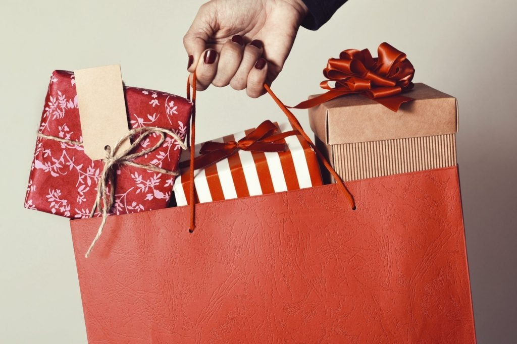 closeup of the hand holding a red shopping bag full of gifts wrapped in different papers